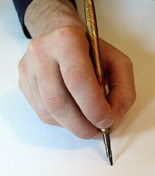 Holding a pen holder in the the closed, upright position.